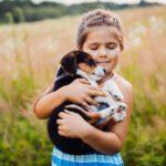 ילדה מחבקת גור בשדה